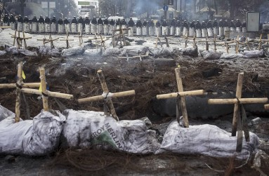 Riot police stand behind crosses installed by anti-government protesters in memory of the people who have died and went missing during clashes in Ukraine, near the barricades in Kiev