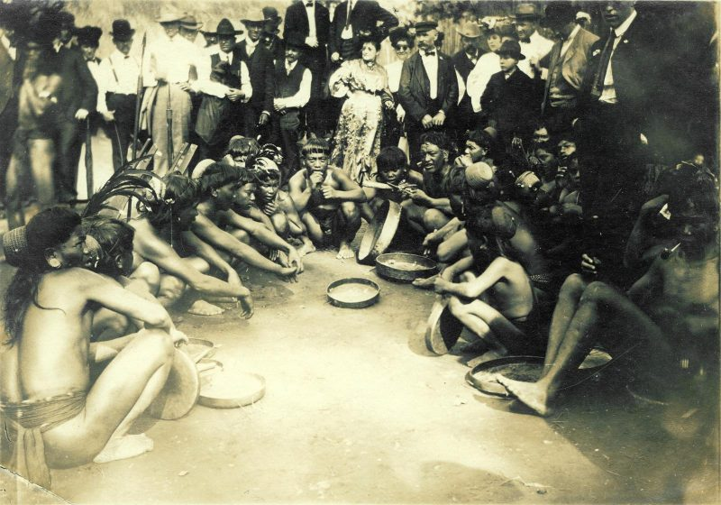 Igorot dancers seated and surrounded by spectators